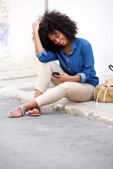 Bllack kobiety obsiadanie ulicą ono uśmiecha się z telefonem komórkowym