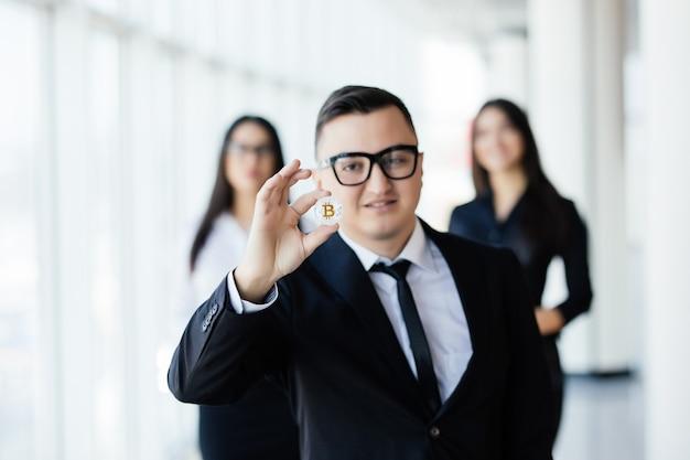 Blockchain i koncepcja inwestycyjna. lider działalności człowieka, trzymając bitcoin przed swoim zespołem w biurze.