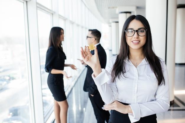 Blockchain i koncepcja inwestycyjna. lider kobieta biznesu trzymając bitcoin przed omawianiem zespołu w biurze.
