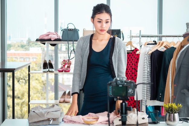 Blog wideo na żywo szczęśliwa młoda dama z azji (vlogger) i sprzedaż ubrań podczas zakupów w sklepie internetowym.