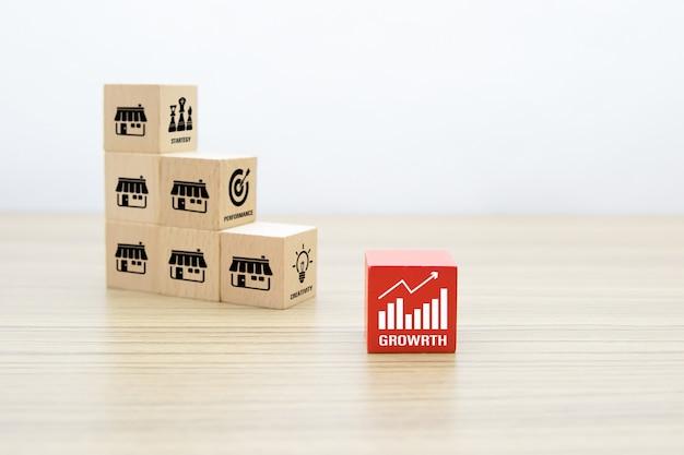 Blog z drewnianymi zabawkami sześcian ułożony z ikoną wykresu i sklepem z ikonami marketingu franczyzowego.