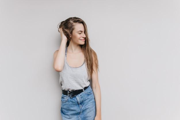 Błoga biała dziewczyna w pozie casualowy strój. kryty strzał szczęśliwa młoda kobieta z długimi fryzurami, wyrażające pozytywne emocje.