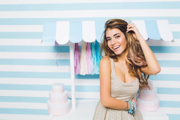 Błoga długowłosa dziewczyna w modnej sukience vintage pozuje z pięknym uśmiechem przed sklepem ze słodyczami. wspaniała młoda kobieta z lśniącymi włosami, stojąca obok kontuaru cukierków na ślicznej pasiastej ścianie.