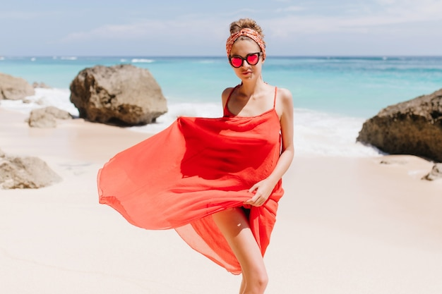 Błoga dziewczyna w błyszczących okularach przeciwsłonecznych bawi się jej długą sukienką na dzikiej plaży. odkryty strzał szczęśliwy dama kaukaski ciesząc się słońcem w ośrodku oceanicznym.