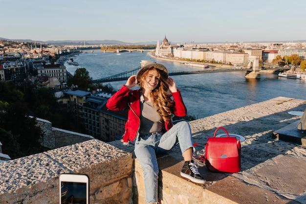 Błoga dziewczyna w ubranie siedzi na dachu i dotyka jej kapelusza