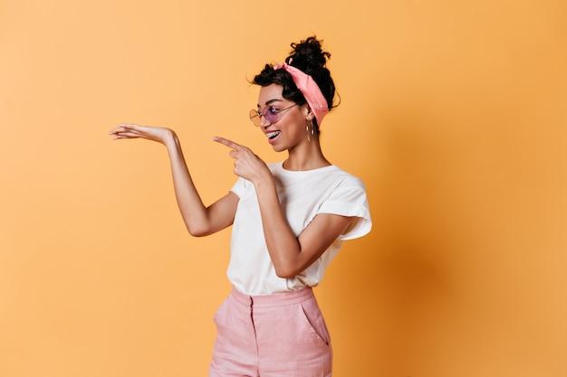 Błoga kobieta gestykuluje na żółtej ścianie z tasiemką
