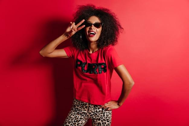 Błoga kobieta śmiejąca się na czerwonej ścianie w modnych okularach przeciwsłonecznych