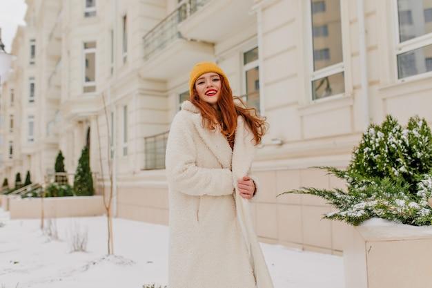 Błoga kobieta w długim płaszczu pozowanie w grudniu. zimowy portret dziewczyny imbiru z wesołym uśmiechem.
