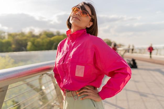 Błoga kobieta w stylowej sportowej różowej kurtce spaceru wcześnie rano