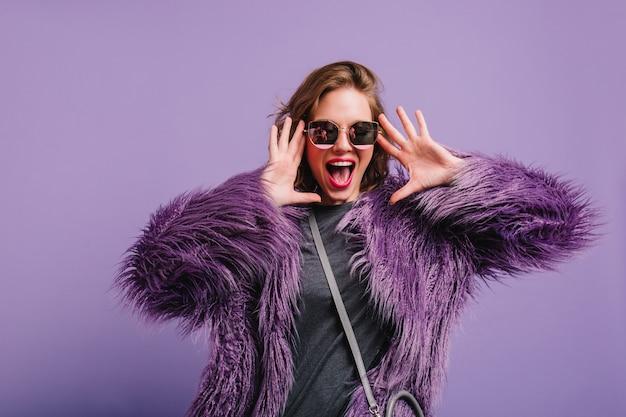Błoga kobieta w szarym stroju i fioletowej kurtce bawi się podczas sesji zdjęciowej w pomieszczeniu