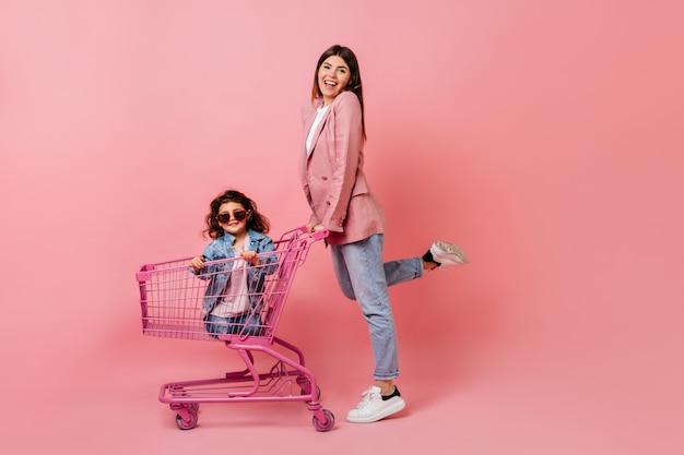 Błoga kobieta z małą córeczką pozuje po zakupach. uśmiechnięta matka stojąca w pobliżu wózka sklepowego.
