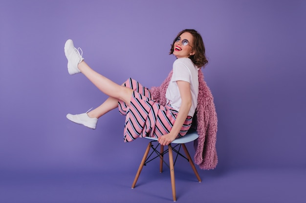 Błoga młoda dama w okularach przeciwsłonecznych wygłupia się podczas sesji zdjęciowej na krześle. śmiejąca się ujmująca dziewczyna w białych butach.