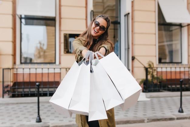 Błoga młoda kobieta w okularach przeciwsłonecznych i długim płaszczu, trzymając paczki podczas ulicznej sesji zdjęciowej