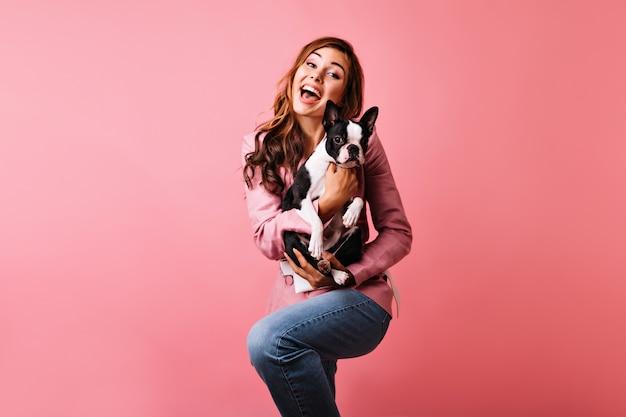 Błoga rudowłosa dama tańczy i trzyma słodkiego psa. wewnątrz portret romantycznej kręconej kobiety wyrażającej pozytywne emocje podczas sesji portretowej z buldogiem francuskim.