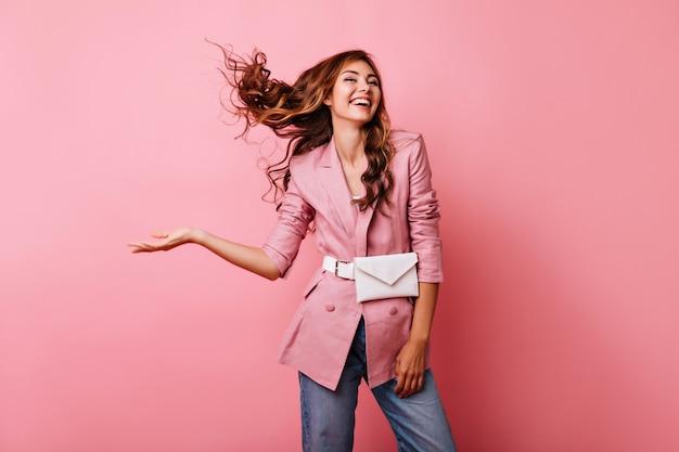 Błoga rudowłosa dziewczyna korzystająca z sesji portretowej. beztroska kaukaska dama w różowej kurtce śmiejąca się na pastelu.