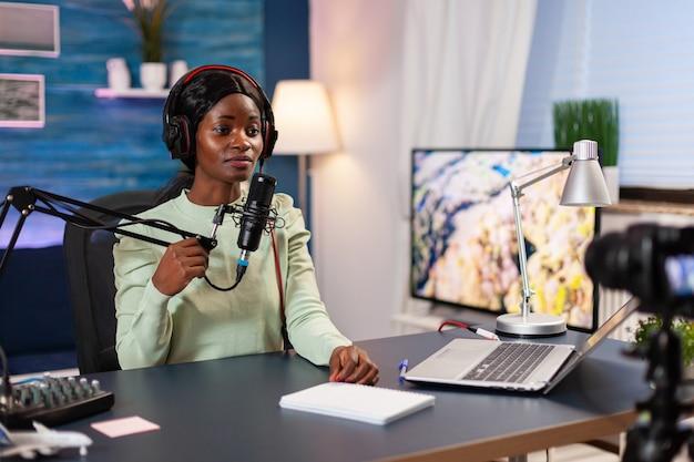 Bloger afro nagrywający podcast rozmawiający do mikrofonu w salonie. przemawiając podczas transmisji na żywo, bloger dyskutujący w podkaście w słuchawkach.