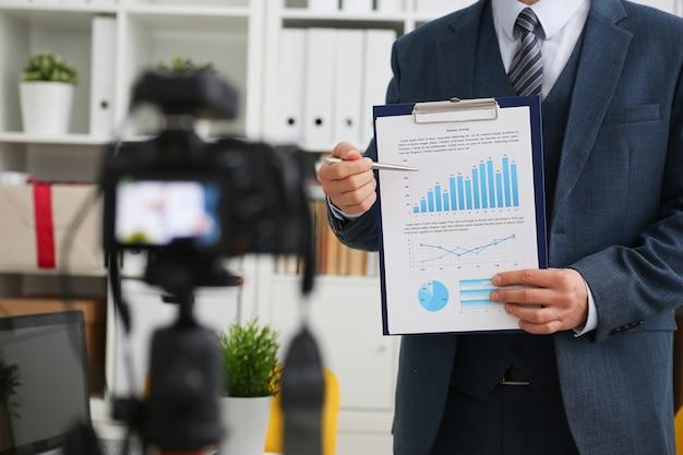 Bloger biznesmen pokazuje wykresy biznesowe za pomocą wskaźników handlowych