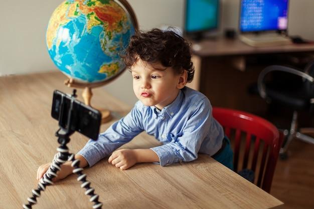 Bloger dziecięcy kręci wideo smartfonem na statywie chłopiec pozuje na smartfonie aparat nagrywa vloga obok kuli ziemskiej zabawny słodki dzieciak