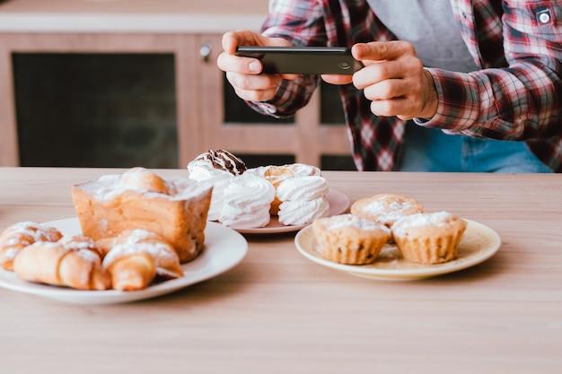 Bloger kulinarny. deser. fotografia mobilna. mężczyzna ze smartfonem robi zdjęcia świeżych domowych wypieków