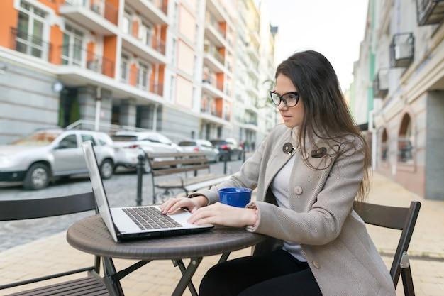 Bloger młoda kobieta w kawiarni na świeżym powietrzu z komputerem