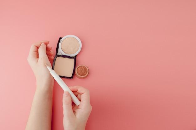 Bloger piękna kobiecych rąk, trzymając butelkę i rurkę spa profesjonalne kosmetyki hi-end na różowym tle, koncepcja minimalizmu, ciepłe, przytulne odcienie i copyspace