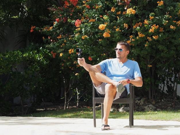 Bloger w ośrodku strzela do kamery. tropikalny ogród kwiatowy. selfie w aparacie.