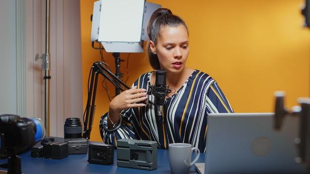 Bloger wideo przeprowadzający porównanie dwóch baterii v-mount w studio. profesjonalna recenzja sprzętu wideo przez twórcę treści, nowego influencera w mediach społecznościowych.