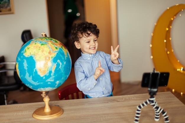 Blogerka dziecięca kręci film smartfonem na statywie, który chłopiec pozuje na aparacie w smartfonie, cho...