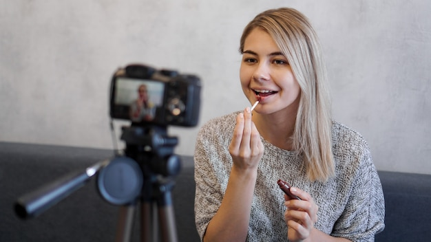 Blogerka kosmetyczna lub blogerka wideo mówi subskrybentom i pokazuje, jak robić makijaż. młoda kobieta maluje usta