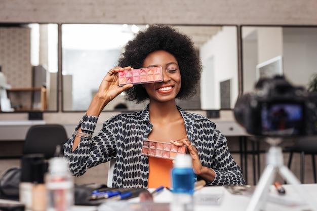 Blogerka makijażu. piękna ciemnoskóra blogerka do makijażu w pomarańczowym topie uśmiecha się przyjemnie podczas pisania posta na bloga