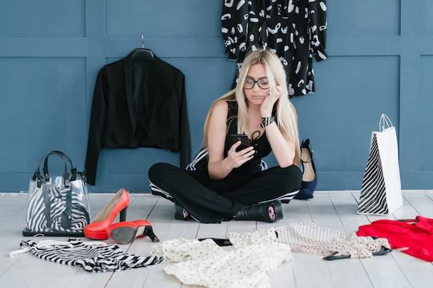 Blogerka modowa z ubraniami na podłodze