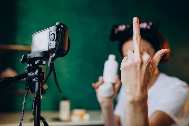 Blogerka o urodzie kobiety filmuje nowy vlog i pokazuje środkowy palec do aparatu