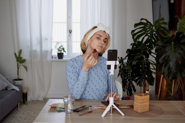 Blogerka piękna nagrywa podcast dla subskrybentów na temat makijażu. koncepcja blogowania, transmisji i kosmetyków