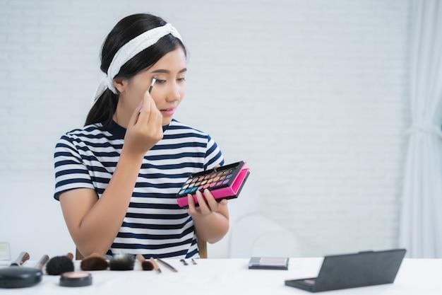 Blogerka piękna przedstawia kosmetyki kosmetyczne siedząc przed kamerą do nagrywania wideo