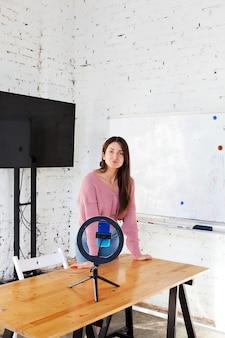 Blogerka prowadzi transmisję na żywo i zapala się lampą pierścieniową w jasnym pokoju