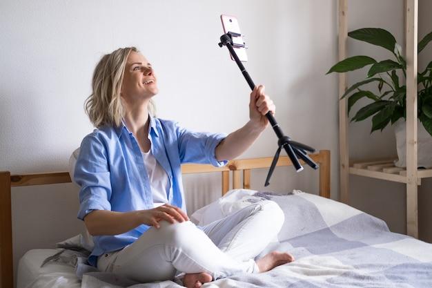 Blogerka rozmawia z obserwującymi, transmituje na żywo, patrzy na ekran smartfona siedząc na łóżku. nawiązywanie połączenia wideo z przyjaciółmi i rodzicami. media społecznościowe, instagram, zostań w domu i poddaj kwarantannie