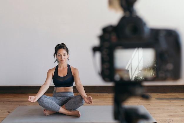 Blogerka zajmująca się jogą nagrywająca wideo w pozie padmasany
