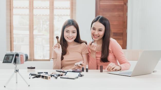 Blogerki kosmetyczne, dwie piękne azjatki, próbują zrozumieć i sprzedać kosmetyki. transmisja strumieniowa online z kamer i laptopów z radosną, uśmiechniętą twarzą, nowa normalna sprawa