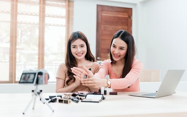 Blogerki kosmetyczne, dwie piękne azjatki, próbują zrozumieć i sprzedać kosmetyki. transmisja strumieniowa online z kamer i laptopów z radosną, uśmiechniętą twarzą - nowy, normalny biznes