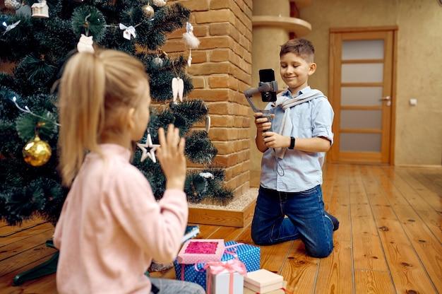 Blogerzy dziecięcy nagrywają świątecznego vloga na telefon. blogowanie dzieci w domowym studio, media społecznościowe dla młodych odbiorców, transmisja internetowa w internecie