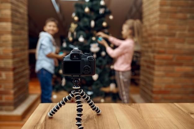 Blogerzy dziecięcy nagrywający bloga świątecznego kamerą, vlogerzy. blogowanie dzieci w domowym studio, media społecznościowe dla młodych odbiorców, transmisja internetowa w internecie