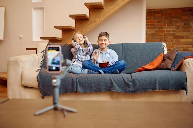 Blogerzy dziecięcy siedzący na kanapie przed kamerą, mali vlogerzy. blogowanie dzieci w domowym studio, media społecznościowe dla młodych odbiorców, transmisja internetowa w internecie