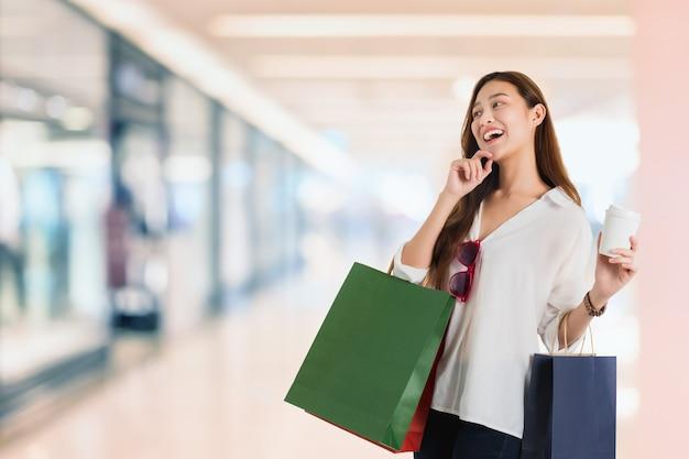 Blogger azjatyckich pięknych kobiet na zakupy i ręka wskazująca z torbą na zakupy w niewyraźne centrum handlowe