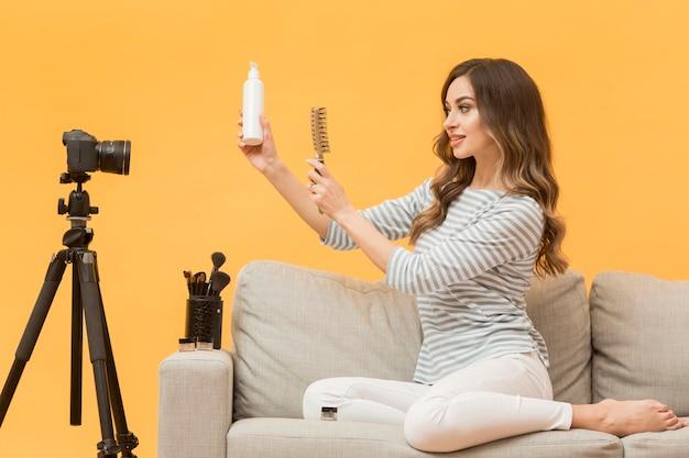 Blogger prezentujący produkty do włosów przed kamerą