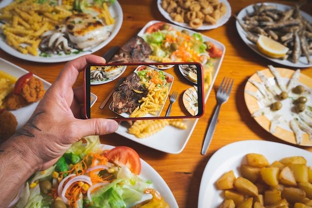 Blogger robi zdjęcie potraw na stole w restauracji