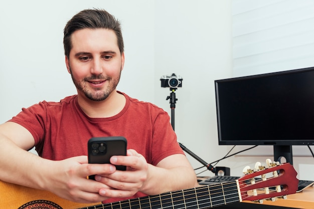 Blogger sprawdza telefon przed lekcją gry na gitarze w swoim domowym studio nagrań