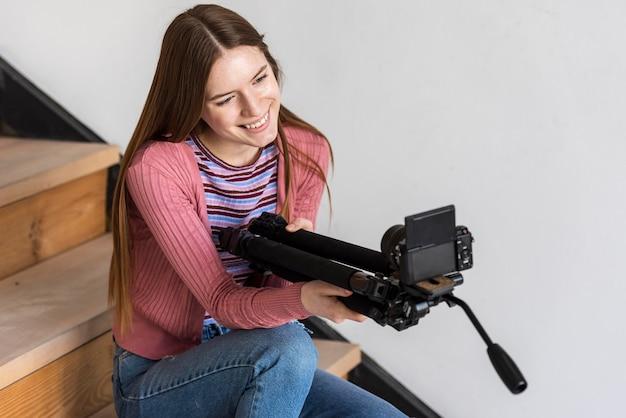 Blogger trzyma statyw z aparatem