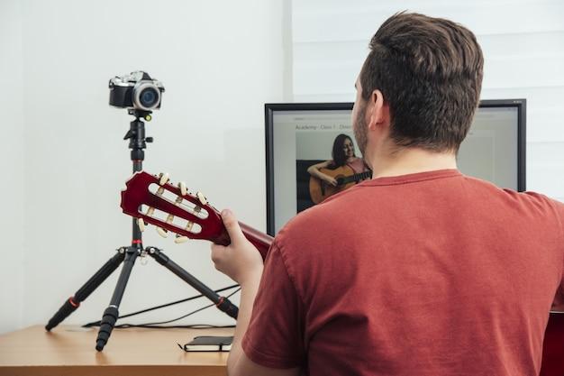 Blogger udzielający lekcji gry na gitarze w swoim domowym studiu nagraniowym