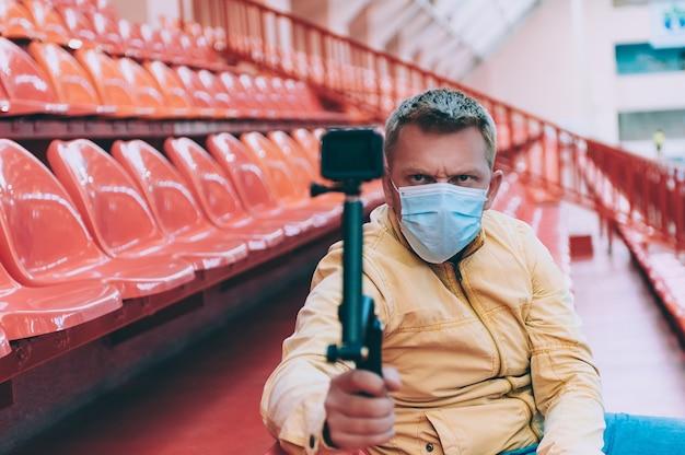 Blogger w masce medycznej na stadionie kręci wideo kamerą sportową.