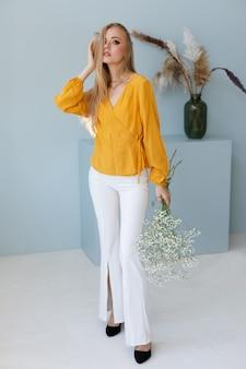 Blogger w stylowym wizerunku z suchymi kwiatami. jesienne ubrania